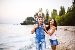 Schöne junge Familie im Urlaub mit Baby Der Vater hält das blonde Mädchen in ihren Armen, und die Brunette ` s Mutter umarmt ihr  Stockfotografie