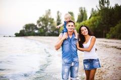 Schöne junge Familie im Urlaub mit Baby Der Vater hält das blonde Mädchen in ihren Armen, und die Brunette ` s Mutter umarmt ihr  Lizenzfreie Stockfotos