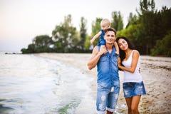 Schöne junge Familie im Urlaub mit Baby Der Vater hält das blonde Mädchen in ihren Armen, und die Brunette ` s Mutter umarmt ihr  Lizenzfreie Stockbilder