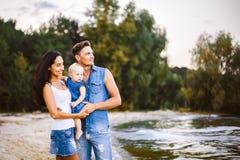 Schöne junge Familie im Urlaub mit Baby Der Vater hält das blonde Mädchen in ihren Armen, und die Brunette ` s Mutter umarmt ihr  Stockfotos
