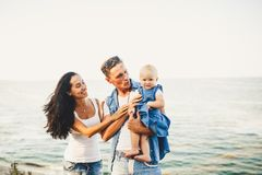Schöne junge Familie im Urlaub mit Baby Der Vater hält das blonde Mädchen in ihren Armen, und die Brunette ` s Mutter umarmt ihr  Lizenzfreies Stockfoto