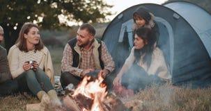 Schöne junge Familie mit einem kleinen Jungen und ihre Freunde haben ein Picknick mit einem Zelt mitten in Natur, sie glücklich stock video footage