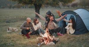 Schöne junge Familie mit ihren Freunden am Picknick, das herum von einem Lagerfeuer, von einem Vati und von einer Mutter spielen  stock footage