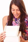 Schöne junge Frau öffnet ein Feriengeschenk lizenzfreie stockfotografie