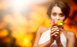 Schöne junge Frau über Herbsthintergrund Stockbilder