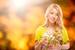 Schöne junge Frau über Herbsthintergrund Stockfotografie