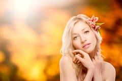 Schöne junge Frau über Herbsthintergrund Lizenzfreie Stockfotografie