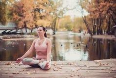 Schöne junge Frau übt Yoga asana auf dem hölzernen Schreibtisch im Herbstpark stockfotografie