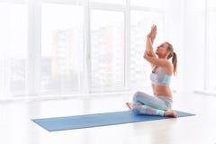 Schöne junge Frau übt Yoga asana Garudasana - Eagle-Haltung am Yogastudio Lizenzfreie Stockbilder