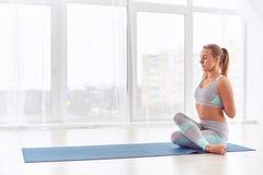 Schöne junge Frau übt Yoga asana Garudasana - Eagle-Haltung am Yogastudio Lizenzfreie Stockfotografie