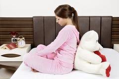 Schöne junge Frau auf Bett stockfotos