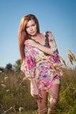 Schöne junge Frau auf dem Gebiet der wilden Blumen auf Hintergrund des blauen Himmels Porträt des attraktiven roten Haarmädchens  Lizenzfreie Stockfotos