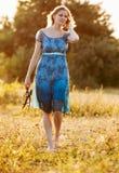Schöne junge Frau auf dem Sommerkleid, das auf dem Gebiet steht Stockfoto