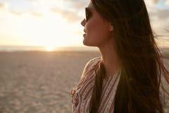 Schöne junge Frau auf dem Strand bei Sonnenuntergang Stockfotos