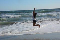 Schöne junge Frau auf dem Strand, der für Freude springt Lizenzfreie Stockbilder