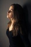 Schöne junge Frau auf einem dunklen Hintergrund Stockfotos