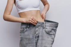 Schöne junge Frau auf einem hellen Hintergrund, Magerkeit, Diät, Gewichtsverlust, Erfolg, Fortschritt Stockfotografie