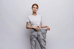 Schöne junge Frau auf einem hellen Hintergrund, verlierendes Gewicht, Diät, Verlust von Kilogramm Stockfoto