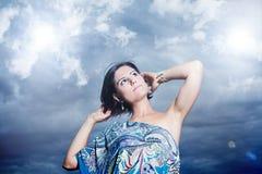 Schöne junge Frau auf einem Hintergrund des Himmels und der Wolken Stockbild