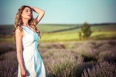 Schöne junge Frau auf einem ländlichen Gebiet voll von Blumen Stockfotografie