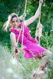Schöne junge Frau auf einem Schwingen Stockbild