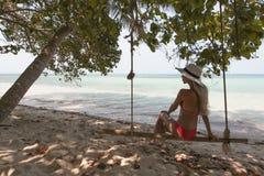 Schöne junge Frau auf einem Schwingen, das auf exotischem Strand stillsteht wellness lebensstil Stockfoto