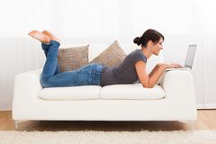 Schöne junge Frau auf einem Sofa Stockbilder