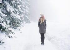 Schöne junge Frau auf einem Weg in der Winternatur Stockbilder