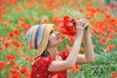 Schöne junge Frau auf Feld mit Mohnblumen Lizenzfreies Stockfoto