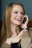 Schöne junge Frau auf Handy Stockbild