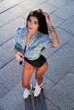Schöne junge Frau auf Rollenrochen lizenzfreies stockfoto