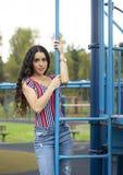 Schöne junge Frau auf Spielplatz stockfoto