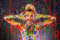 Schöne junge Frau bedeckt mit Farben lizenzfreie stockfotos