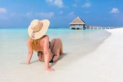 Schöne junge Frau, beim sunhat Sitzen entspannte sich auf tropischem Strand in Malediven Lizenzfreie Stockfotos