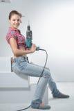 Schöne junge Frau benutzt eine elektrische Bohrmaschine Stockbilder