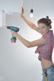 Schöne junge Frau benutzt eine elektrische Bohrmaschine Lizenzfreies Stockfoto