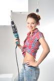 Schöne junge Frau benutzt eine elektrische Bohrmaschine Stockbild