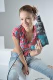 Schöne junge Frau benutzt eine elektrische Bohrmaschine Stockfotos