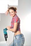 Schöne junge Frau benutzt eine elektrische Bohrmaschine Lizenzfreies Stockbild