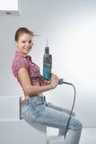 Schöne junge Frau benutzt eine elektrische Bohrmaschine Stockfotografie