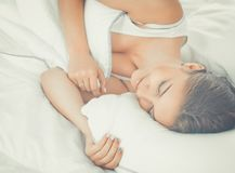 Schöne junge Frau bequem und, die himmlisch im Bett liegt stockfoto