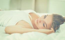 Schöne junge Frau bequem und, die himmlisch im Bett liegt lizenzfreie stockfotos