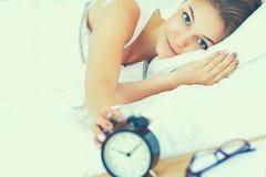 Schöne junge Frau bequem und, die himmlisch im Bett liegt stockbilder