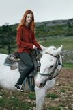 Schöne junge Frau in den Bergen gehend mit ihrem Pferd Lizenzfreies Stockfoto