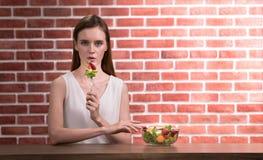 Schöne junge Frau in den frohen Lagen mit der Hand, die Salat hält stockfotos
