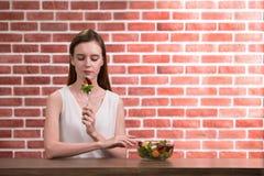 Schöne junge Frau in den frohen Lagen mit der Hand, die Salat hält lizenzfreie stockfotos