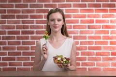 Schöne junge Frau in den frohen Lagen mit der Hand, die Salatschüssel hält stockfotos