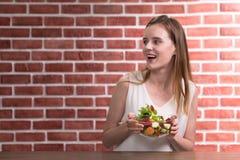 Schöne junge Frau in den frohen Lagen mit der Hand, die Salatschüssel hält lizenzfreies stockbild