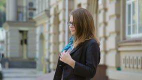 Schöne junge Frau in den Gläsern gehend auf die Straße stock video
