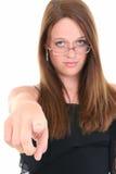 Schöne junge Frau in den Gläsern zeigend in Richtung zur Kamera Stockbild